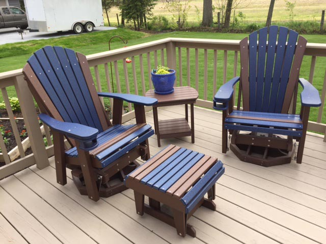 Adirondack Swivel Gliders w/Cupholders and a Gliding Ottoman, shown in Blue on Brown, and an Oval End Table Shown in Brown.