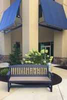 five foot poly garden bench shown in weatherwood on blue