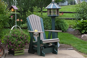 adirondack glider w/ cupholder shown in weatherwood on green